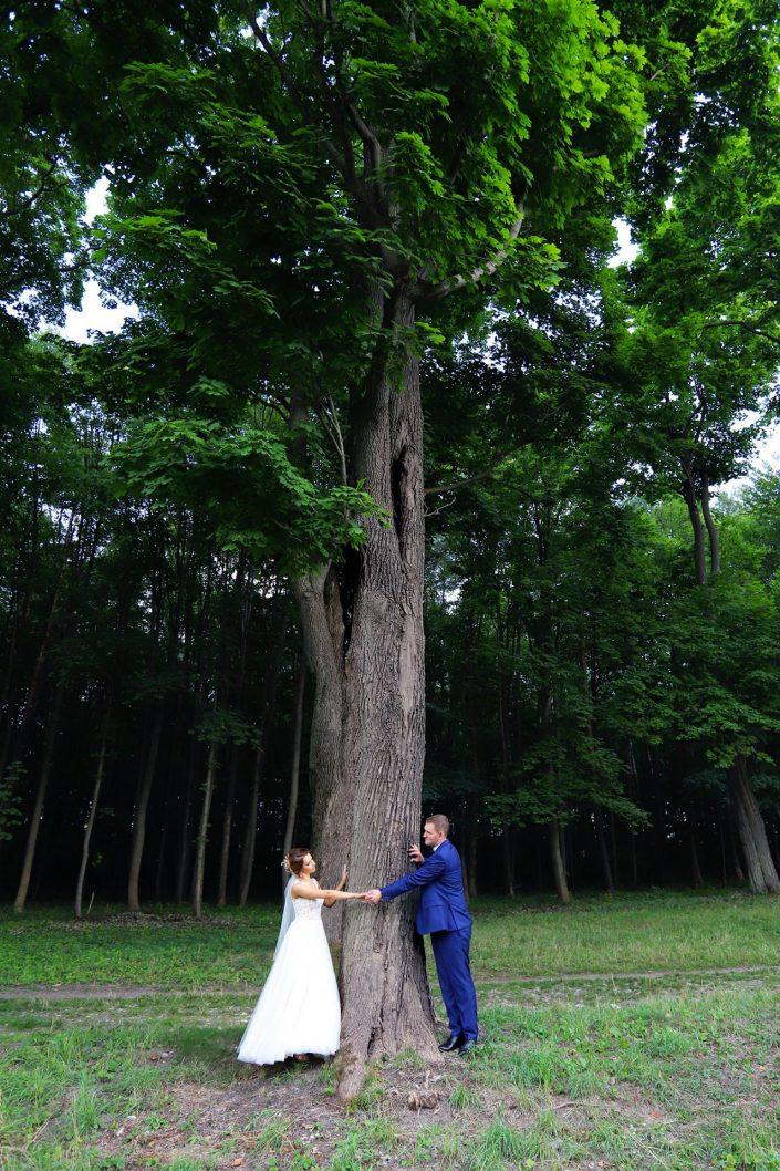 Para młoda stojąca przy drzewie