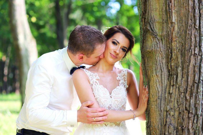 Para młoda opierająca się o drzewo