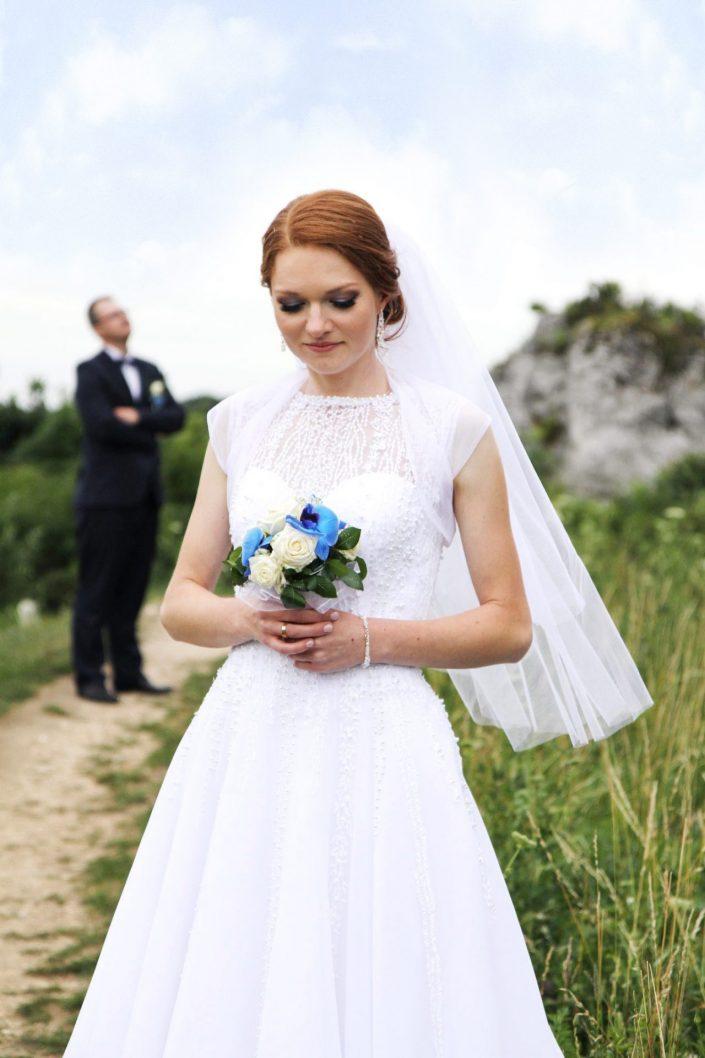 Panna młoda patrząca się na bukiet ślubny