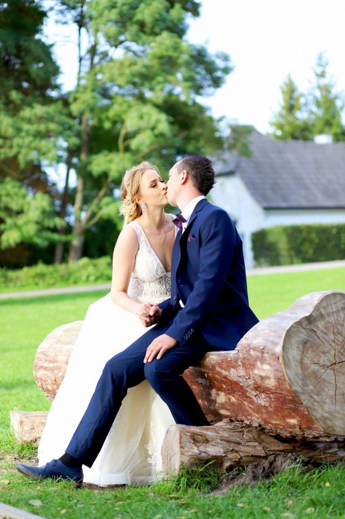 Para młoda siedząca na drewnianej ławce